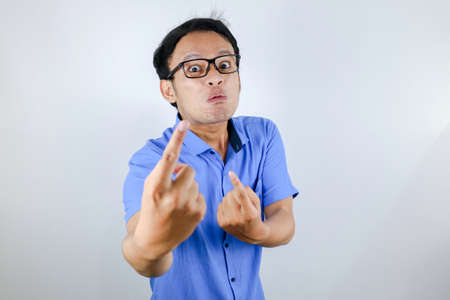 Young Asian Man wear blue shirt is funny angry face with shouting and pointing finger at camera isolated over white background
