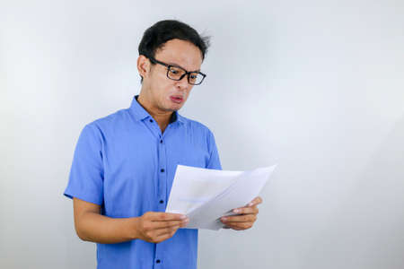 Young Asian Man is mad and angry when looking on paper document. Indonesian man wearing blue shirt.