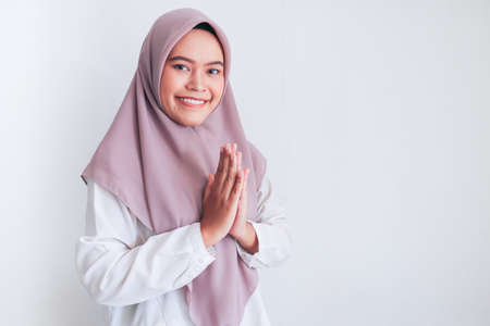 Young Asian Islam woman wearing headscarf gives greeting hands at with a big smile on her face. Indonesian woman on gray background. Eid Mubarak greeting.