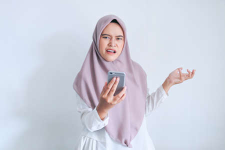 Young Asian Islam woman wearing headscarf is shocked disgusted and angry in what she see on the smartphone. Indonesian woman on gray background.