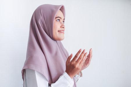 头巾和hijab的亚裔伊斯兰教穆斯林妇女用她的手在空气中祈祷与微笑面孔。印度尼西亚女人。在灰色背景隔绝的宗教祈祷的概念。