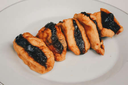 Fried tofu or tahu with petis sauce in white platebackground, javanese traditional indonesian snack.