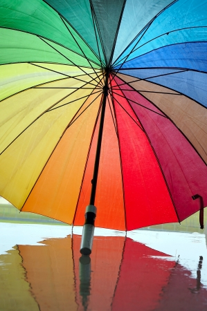 Opened multi-colored umbrella with reflection.                                 photo