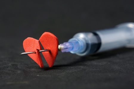 Injection into red heart with syringe on black background       photo