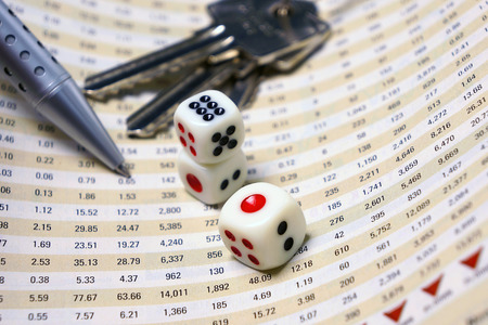 Dices on financial report with pen and keys for business concept