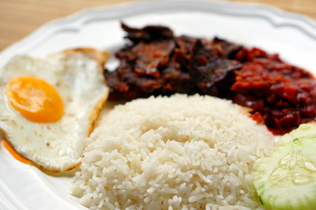 nasi: Nasi lemak (coconut rice) served with sunny side up egg, hot spicy fried beef lungs and hot spicy sauce. Nasi lemak is a fragrant rice dish cooked in coconut milk Stock Photo