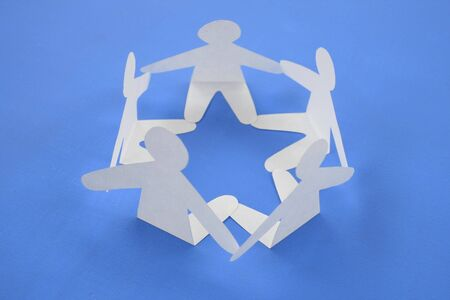Silhouettes of figures of the person sit in a circle, having joined hands. Stock Photo - 4149935