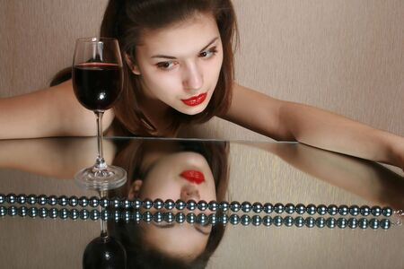 Portrait of the girl with a glass of wine and reflection in a mirror. photo