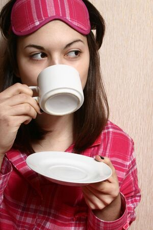 Portrait of the girl in the pink pajamas, enjoying morning coffee. Stock Photo - 4153355