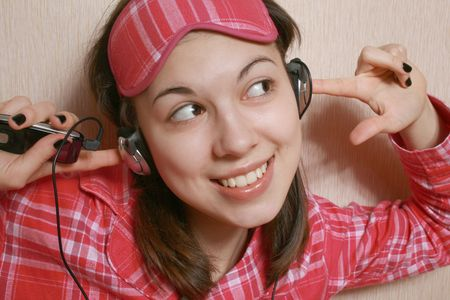 Portrait of the girl in a pink pajamas and headphones. Stock Photo - 4153356