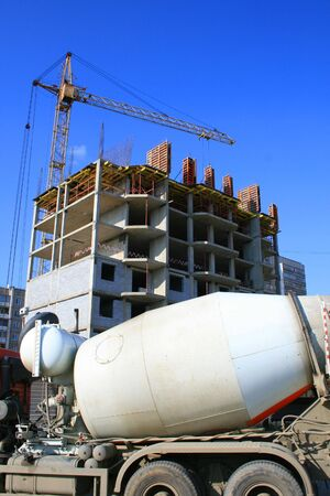 The image of construction of a building and the tower crane.