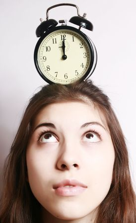 beat the clock: The image of an alarm clock costing on a head of the girl.