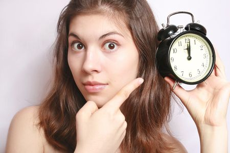 past midnight: Portrait of the girl showing a finger on an alarm clock. Stock Photo