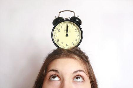 Het beeld van een wekker kostenberekening op een hoofd van het meisje. Stockfoto