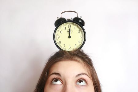 past midnight: The image of an alarm clock costing on a head of the girl.