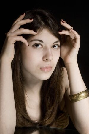 Portrait of the young brunette on a black background. Stock Photo - 5406409