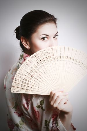 Portrait of the girl in east dressing gown and a fan in a hand.