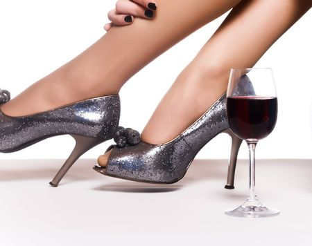 Female legs in shoes on a high heel and a glass of red wine.  photo