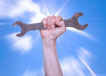 Hand met een moersleutel op een achtergrond van de sprankelende hemel.