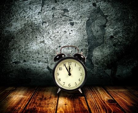 reloj pared: Reloj de alarma sobre un fondo de una antigua muralla.  Foto de archivo