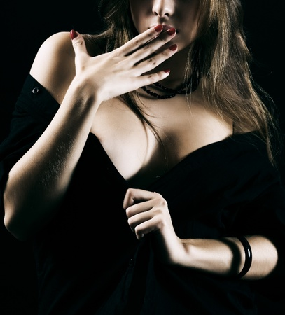 unexpectedness: The magnificent woman with beautiful hands on a black background.