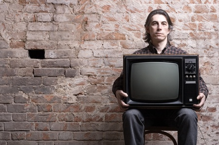 A man holding a retro television set sitting on a background of brick wall