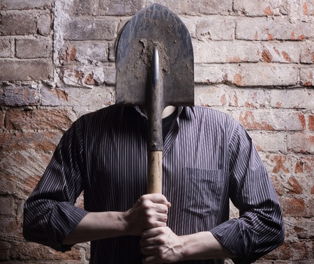 inconspicuous: A man hides his face behind a shovel. Depersonalization, a metaphor.