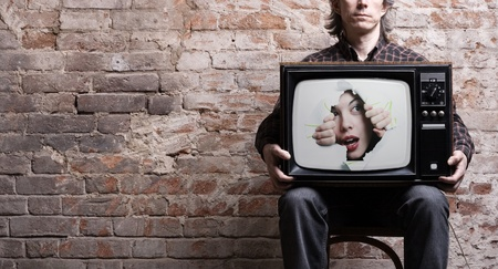 woman watching tv: TV with a picture of the girl -facing through a hole in the hands of a seated man .