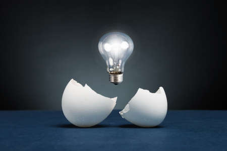 innovation technology: From the broken egg the shone lamp is pulled out. Stock Photo