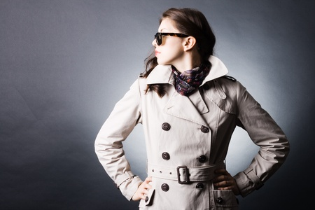 Fashion portrait of young beautiful woman in the raincoat and sunglasses photo