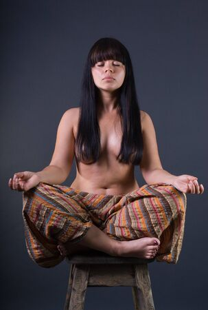 Portrait of young woman meditating in pose of lotus photo
