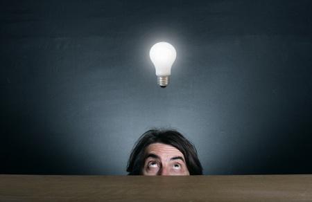 Man looking up at the burning light bulb. photo