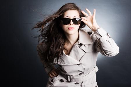 Fashion portret van jonge mooie vrouw in de regenjas en een zonnebril Stockfoto