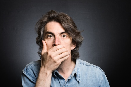 scared man: scared adult man with hand covering mouth and dramatic lighting Stock Photo