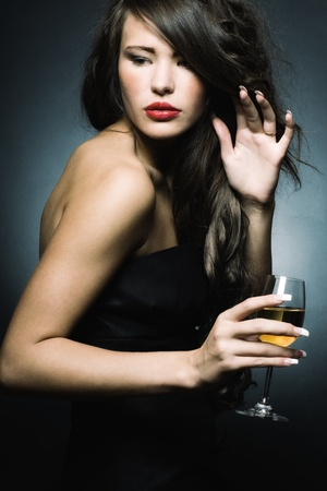 Beautiful sexy woman with a glass of white wine on a dark background. Stock Photo