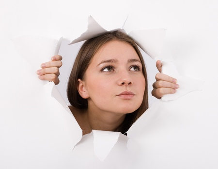 The girl spies through a hole in a paper. Stock Photo - 10936632