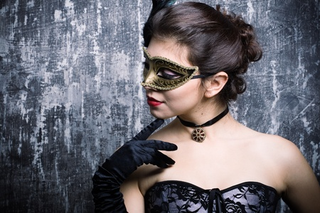The beautiful young girl in a mysterious mask photo