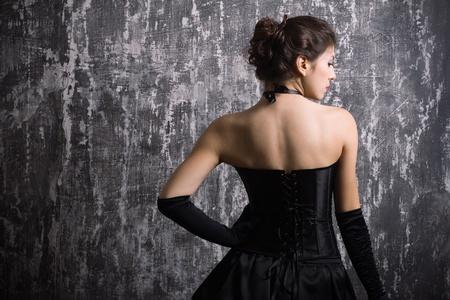 Schöne modische Frau im schwarzen Kleid.
