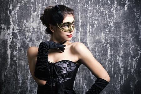 De mooie jonge meisje in een mysterieus masker Stockfoto