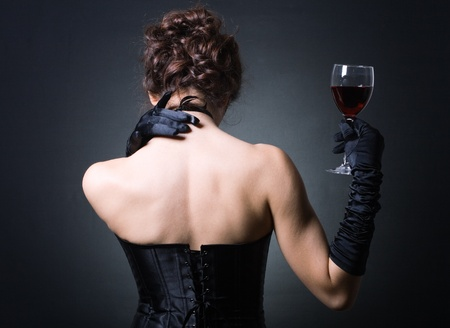 Fashion photo of young ladies in elegant evening dress with a glass of red wine.