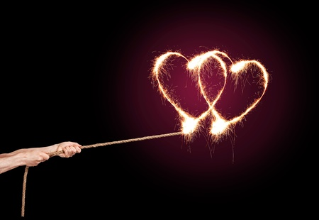 Sparkling Love Heart pulls a pair of hands at the rope. photo