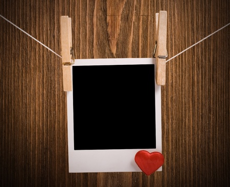 wooden insert: Blank instant photo and small red heart hanging on the clothesline. On dark grunge background.
