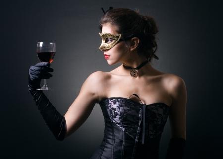 jeune femme dans masque de carnaval et un verre de vin rouge. Banque d'images