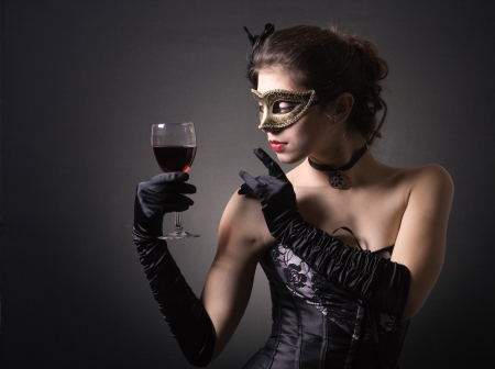 young woman in carnival mask and a glass of red wine. 版權商用圖片