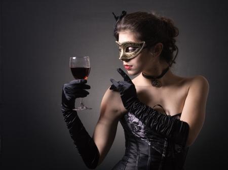 jonge vrouw in carnaval masker en een glas rode wijn.