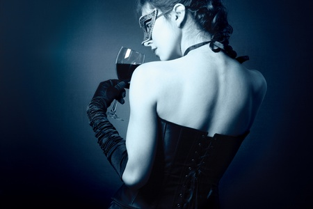 young woman in carnival mask and a glass of red wine. Stok Fotoğraf