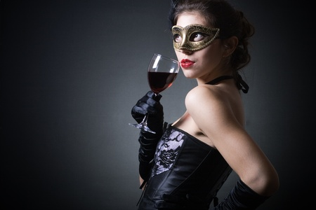 young woman in carnival mask and a glass of red wine. photo