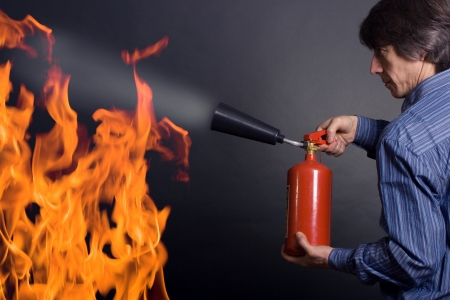 man with extinguisher fighting a fire Stock Photo