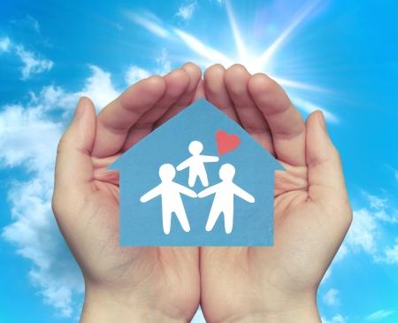 La familia en la casa. Manos sosteniendo una casa con una familia feliz contra el telón de fondo del cielo soleado.