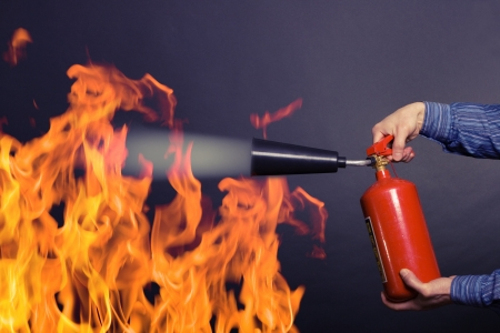 man with extinguisher fighting a fire photo